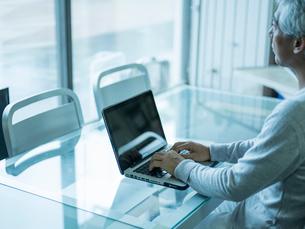 ノートパソコンを操作するシニア男性の写真素材 [FYI02057643]