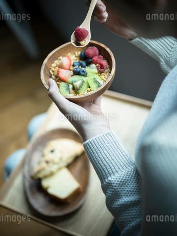 フルーツグラノーラを食べる女性の手元の写真素材 [FYI02057644]