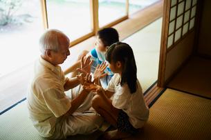 あやとりをする祖父と孫たちの写真素材 [FYI02057650]