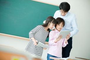教室でタブレットPCを見る小学生の女の子と男の子と先生の写真素材 [FYI02057656]
