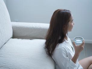 ソファに寄りかかりグラスを持つ女性の写真素材 [FYI02057659]