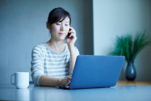 ノートパソコンを見ながら電話をする女性の写真素材 [FYI02057661]
