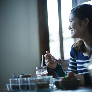 朝食を食べる女性の横顔の写真素材 [FYI02057699]