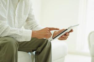 タブレットPCを操作する男性の手元の写真素材 [FYI02057700]