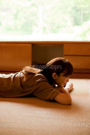 床に寝転ぶ女性の写真素材 [FYI02057720]