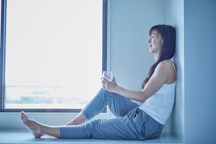 休憩するトレーニングウェア姿のミドル女性の写真素材 [FYI02057741]