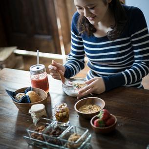 フルーツグラノーラヨーグルトを食べる女性の写真素材 [FYI02057760]