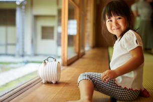 縁側に座る女の子と蚊取り豚の写真素材 [FYI02057774]