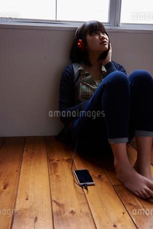 スマートフォンで音楽を聴く10代女性の写真素材 [FYI02057787]