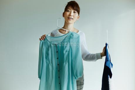 洋服を身体にあててみる女性の写真素材 [FYI02057791]