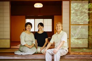 縁側に座る娘と両親の写真素材 [FYI02057810]