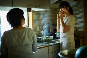キッチンで枝豆を食べる娘と母親の写真素材 [FYI02057814]