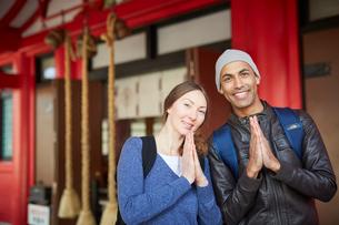 神社で手を合わせる外国人カップルの写真素材 [FYI02057820]