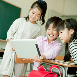 教室でタブレットPCを操作する小学生3人の写真素材 [FYI02057858]