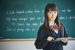 黒板の前でタブレットPCを持つ女子学生の写真素材 [FYI02057869]
