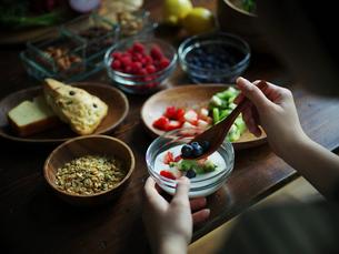 フルーツグラノーラヨーグルトを食べる女性の手元の写真素材 [FYI02057874]