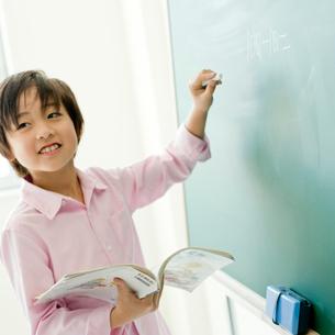 黒板の前に立つ小学生の男の子の写真素材 [FYI02057877]