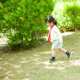 新緑の公園を歩く女の子の写真素材 [FYI02057882]