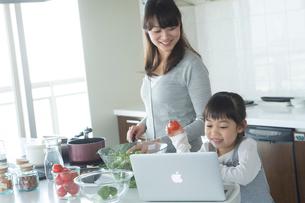 キッチンでノートパソコンを見ながら料理をする母親と女の子の写真素材 [FYI02057889]