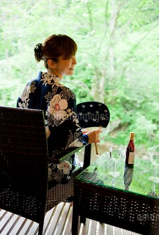 団扇を持ち椅子に座る浴衣姿の女性の写真素材 [FYI02057931]