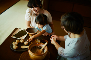 おにぎりを作る三世代女性ファミリーの写真素材 [FYI02057935]