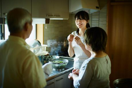 キッチンで談笑する女性と両親の写真素材 [FYI02057945]