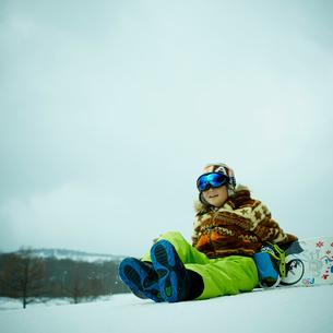 雪の上に座る男の子とスノーボードの写真素材 [FYI02057950]