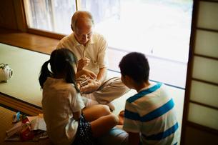 あやとりをする祖父と孫たちの写真素材 [FYI02057955]