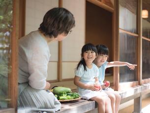 縁側に座る祖母と女の子2人の写真素材 [FYI02057962]