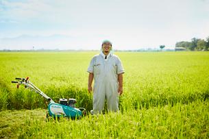 稲田に立つ笑顔の農夫の写真素材 [FYI02057963]