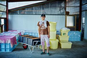 梅干し作りの作業場に立つ笑顔の男性の写真素材 [FYI02057969]