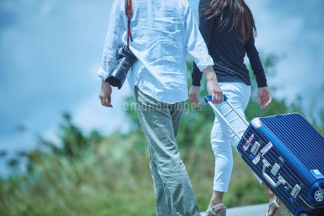 スーツケースをひいて歩くミドル夫婦の写真素材 [FYI02057986]