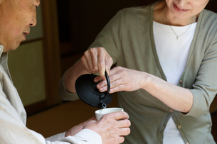 急須でお茶を淹れるシニア夫婦の手元の写真素材 [FYI02057991]