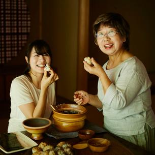 おにぎりを食べる娘と母親の写真素材 [FYI02058018]