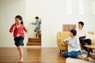 リビングルームで走り回る子供達とくつろぐ両親の写真素材 [FYI02058032]