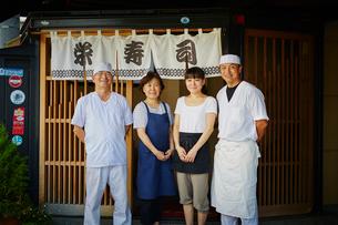 寿司屋の前に並んで立つ寿司職人と店員の写真素材 [FYI02058039]