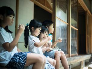 縁側でおにぎりを食べる子供たちの写真素材 [FYI02058070]