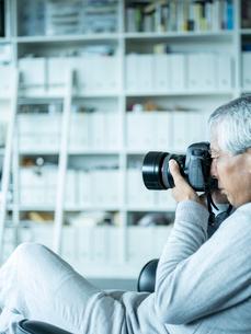 カメラを構えるシニア男性の写真素材 [FYI02058091]