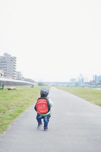道を歩くリュックを背負った男の子の後ろ姿の写真素材 [FYI02058104]