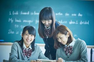 タブレットPCを見る3人の女子学生の写真素材 [FYI02058114]