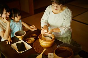 おにぎりを作る三世代女性ファミリーの写真素材 [FYI02058125]