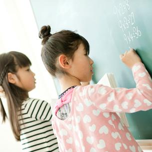 黒板で算数の問題を解く小学生の女の子2人の写真素材 [FYI02058133]