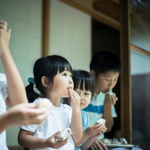 縁側でおにぎりを食べる子供たちの写真素材 [FYI02058136]