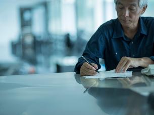 書類を書くシニア男性の写真素材 [FYI02058141]