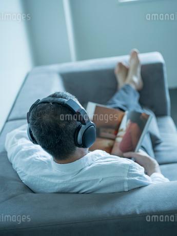 ヘッドフォンをつけて本を読むミドル男性の写真素材 [FYI02058154]