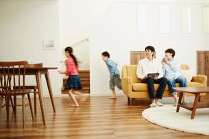 リビングルームで走り回る子供達とソファに座る両親の写真素材 [FYI02058200]