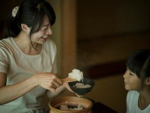 ご飯をよそう母親と女の子の写真素材 [FYI02058207]