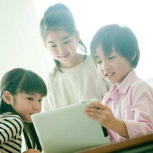 教室でタブレットPCを操作する小学生3人の写真素材 [FYI02058210]