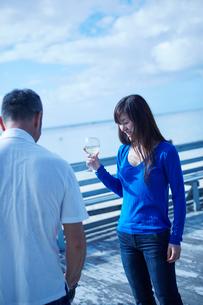 ワイングラスを持つミドル女性と男性の後ろ姿の写真素材 [FYI02058217]