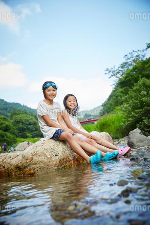 河原に座る女の子2人の写真素材 [FYI02058221]